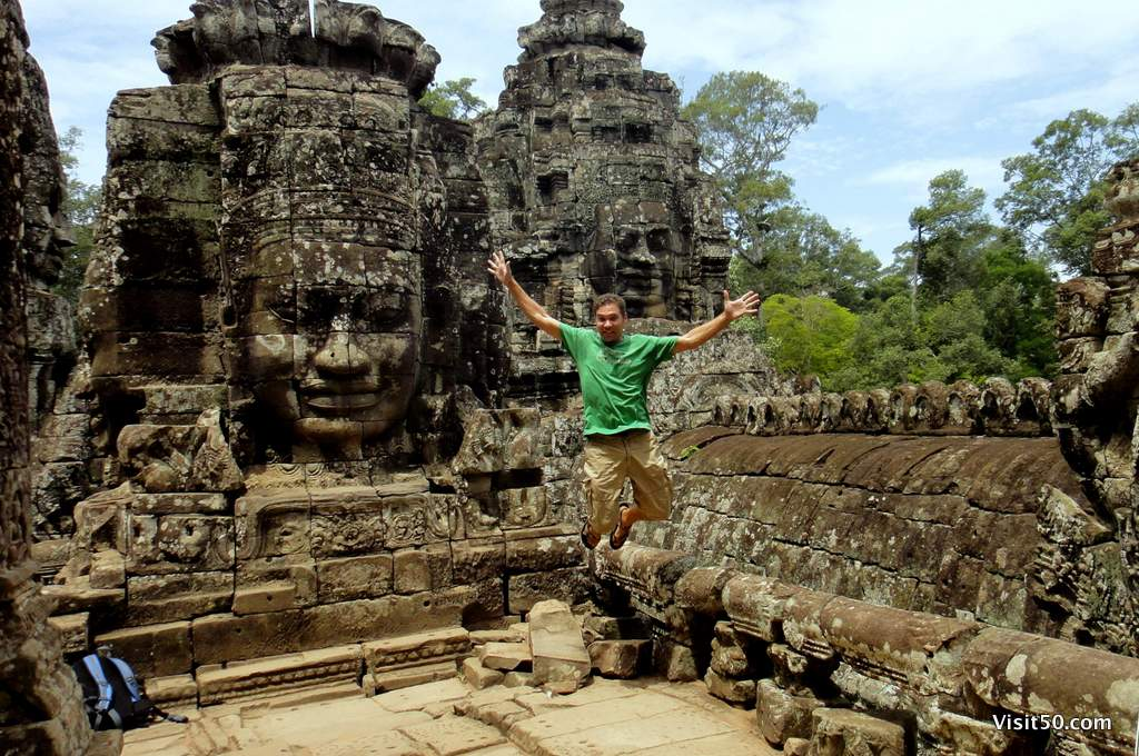Jumping in Cambodia! These are 2 of the 216 huge face sculptures in the Bayon section of the Angkor complex.